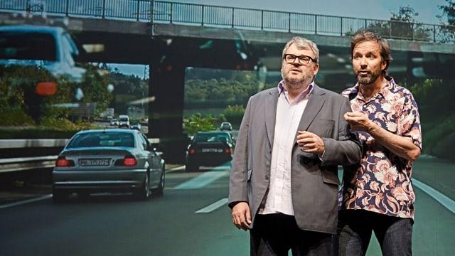 Zwei Männer stehend vor einer Projektion der Autobahn hinter ihnen.