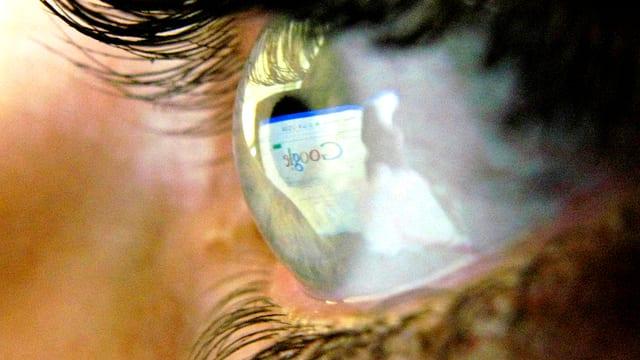 Nahaufnahme eines Auges, in dem sich ein Bildschirm mit der Google-Seite spiegelt.