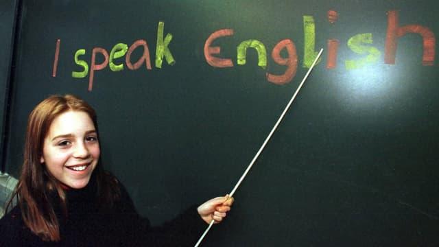 """Schülerin zeigt mit Stock auf eine Wandtafel, wo geschrieben steht """"I speak English"""""""