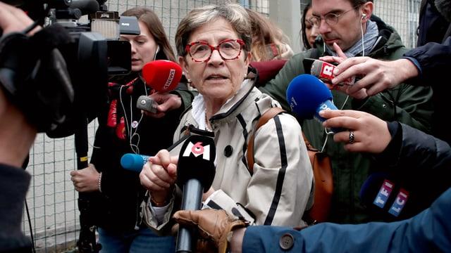 Viviane Lambert umringt von Reportern mit Mikrofonen.