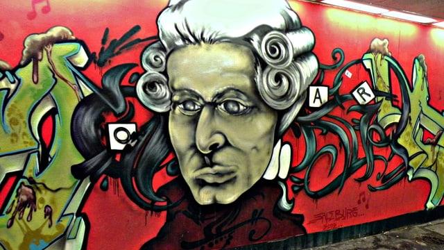 Ein buntes Graffito von Mozart auf rotem Hintergrund in einer Strassenunterführung.