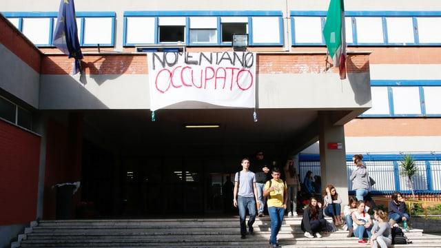 Eine Schule mit einer grossen Treppe, auf der ein paar junge Leute stehen und sitzen, ein grosses Transparent hängt an einer Terasse.
