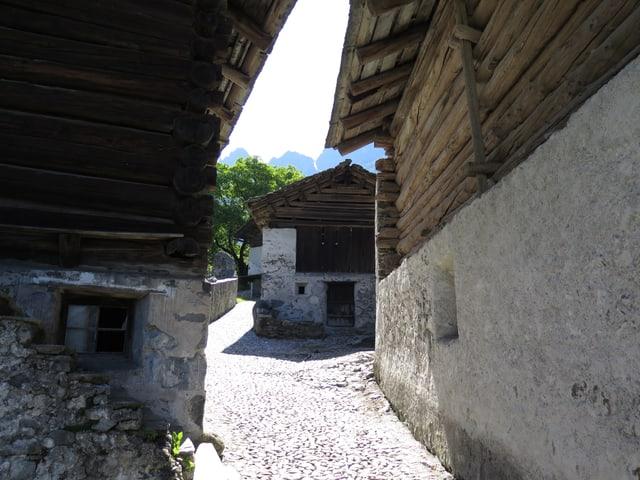 Ein Blick in eine Gasse mit Maiensäss-Häusern auf der linken und rechten Seite.