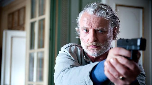 Ein Mann mit grauen Haaren und Bart zielt mit der Waffe auf ein unbekanntes Ziel.