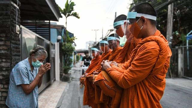 Buddhistische Mönche sammeln Almosen mit Gesichtsschutz.