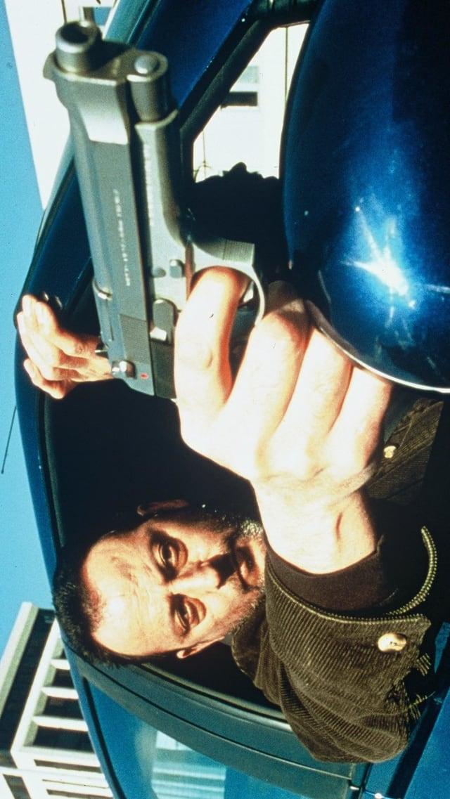 Ein Mann lehnt sich mit gezückter Pistole aus dem Auto.