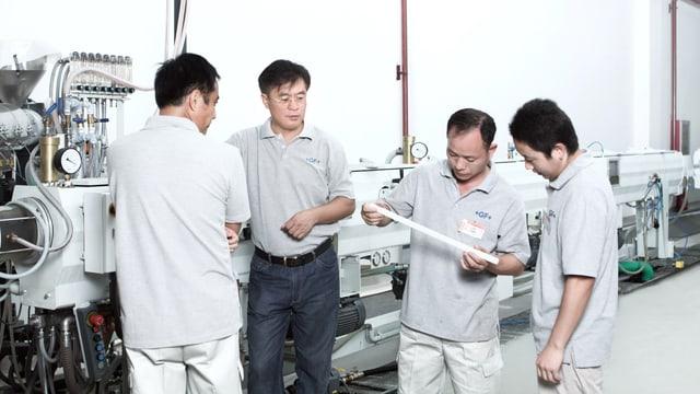 Chinesische GF-Mitarbeiter bei einer Produktionskontrolle.