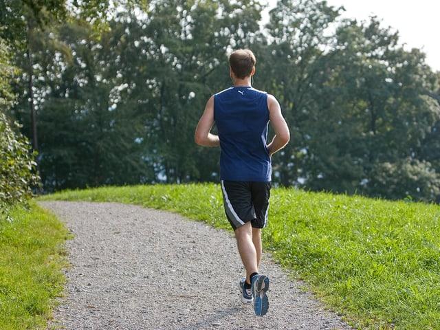 Junger Mann joggt über einen Kiesweg.