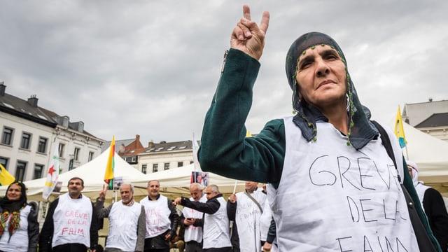 Im Vordergrund eine ältere Frau, sie macht ein Victory-Zeichen und trägt ein Shirt, auf dem steht «grève de faim», hinter ihr weitere Frauen und Männer mit gleichen Shirts.