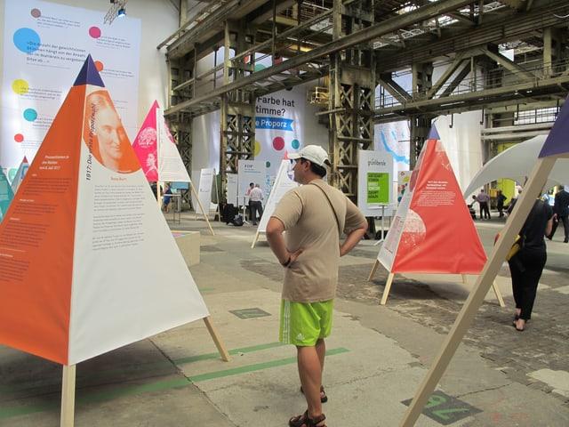 Blick in die Halle in der mit Holzstangen Stoffpyramiden mit aufgedruckten Informationen aufgestellt sind.