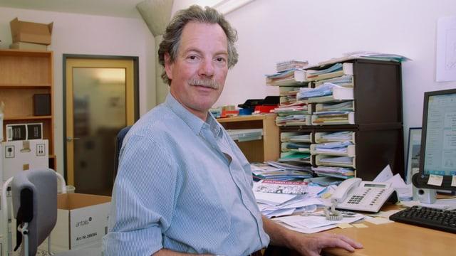 Hansueli Probst sitzt an seinem Bürotisch. Im Hintergrund stehen Regale mit viel Papier und Umzugskartons.