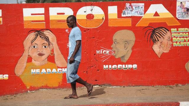 Ein Mann läuft in Monrovia an einer Mauer vorbei, auf die Vorsichtsmassnahmen gegen Ebola gemalt wurden.