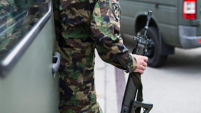 In schuldà svizzer tegna in'arma en il maun.