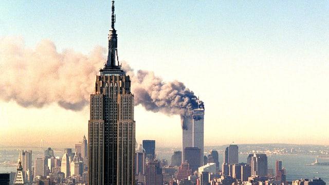 Vogelperspektive der Stadt New York - im Hintergrund raucht ein Hochhaus.