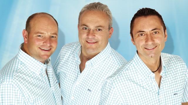 Pressefoto mit drei Männern, die alle ein helles kariertes Hemd tragen.