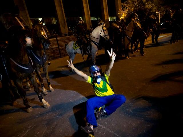 Ein Demonstrant macht das Siegeszeichen. Im Hintergrund berittene Polizei.