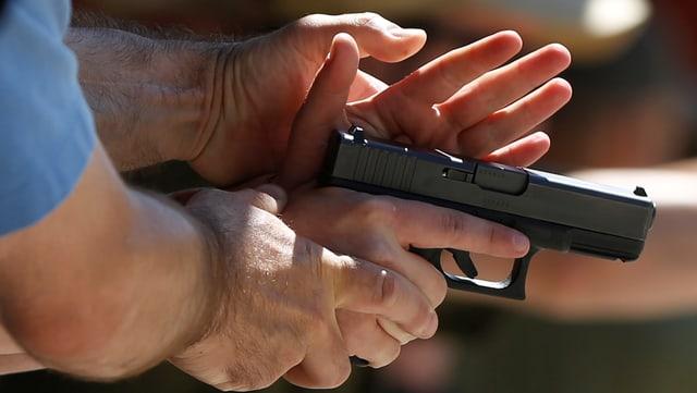 Mann hält Pistole in der Hand.