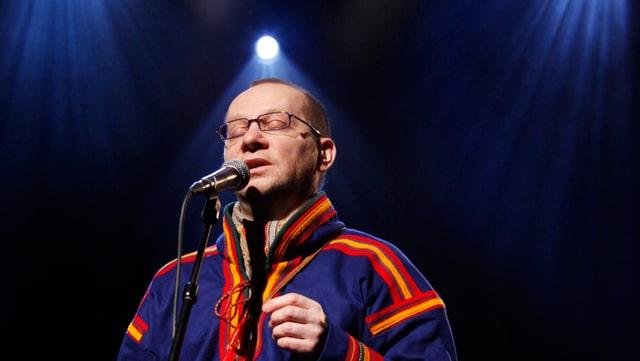 Wimme in traditioneller blauer Samen-Kleidung steht mit geschlossenen Augen vor einem Mikrofon.