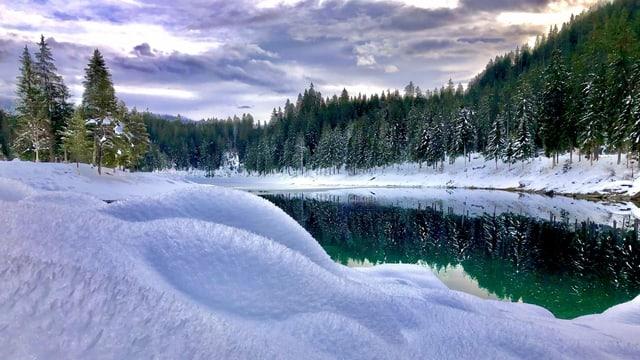 Verschneite Landschaft rund um den See.