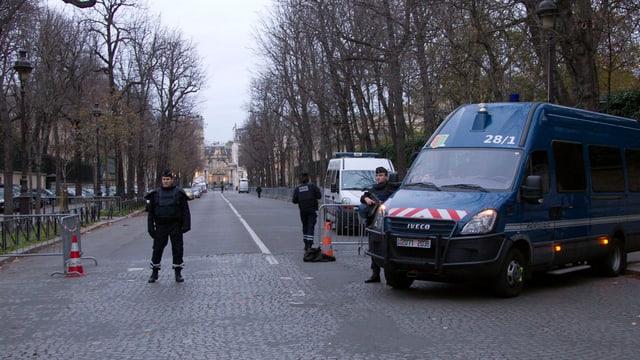 Kastenwagen der Polizei rechts, leere Strasse, ein Polizist steht auf dem Fahrstreifen.