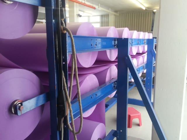 Von aufgehängten Rollen werden die Papierschichten laufend abgerollt und zum Stanzen vorbereitet.