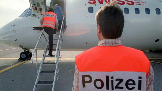 Polizisten überwachen eine Zwangsausschaffung per Flugzeug.