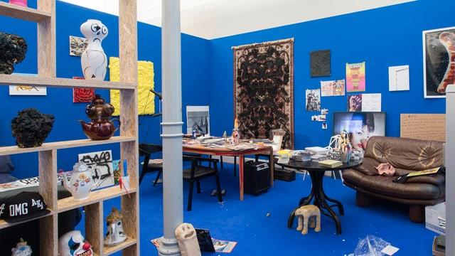 Zimmer mit blauen Wänden, vollgestopft mit Gegenständen.