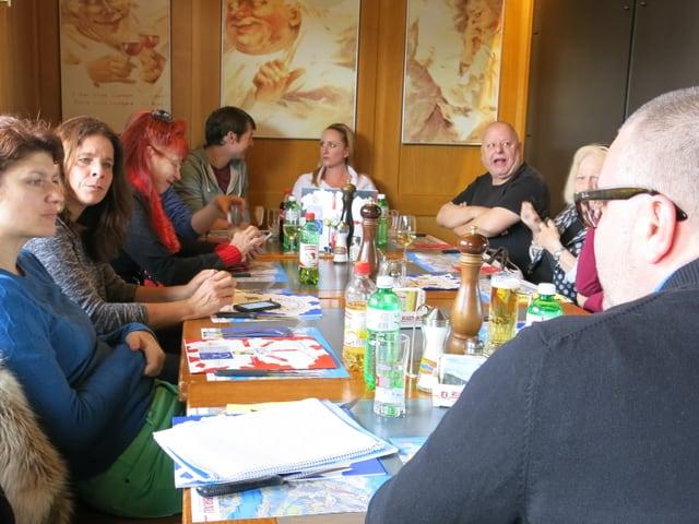 Menschen sitzen um einen Tisch.