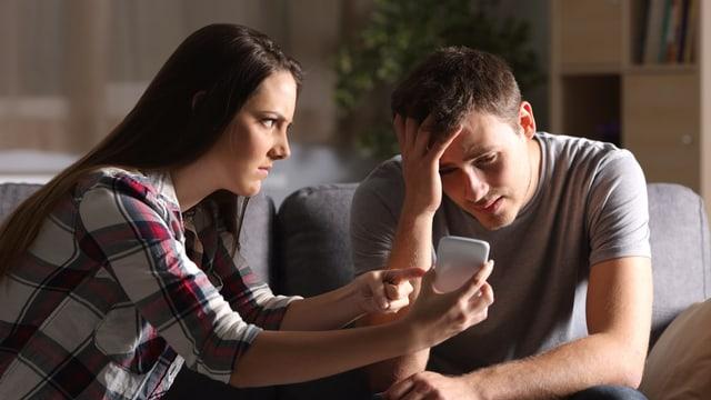 Eine Frau hält ihrem Partner das Smartphone vors Gesicht und macht einen vorwurfsvollen Gesichtsausdruck.