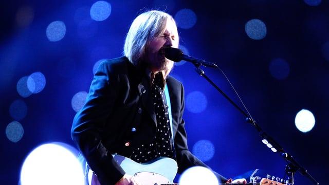 Ein Mann auf einer Bühne mit Gitarre.