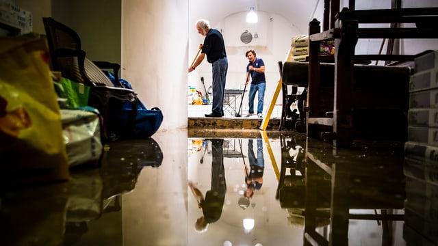 Zwei Männer räumen nach Überschwemmungen den Keller auf