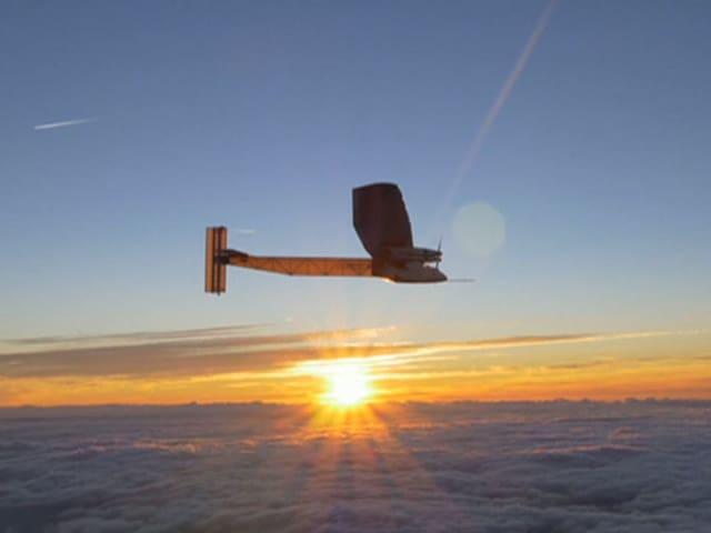 Wolkendecke, Sonnenuntergangsstimmung, im blauen Himmel fliegt das Solarflugzeug