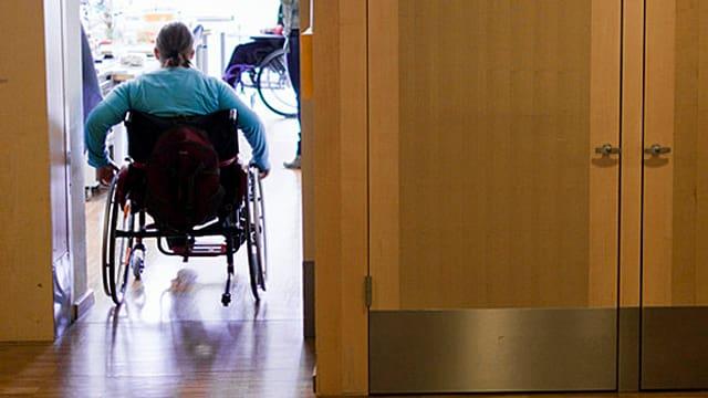 Ein Rollstuhlfahrer fährt durch eine Tür.
