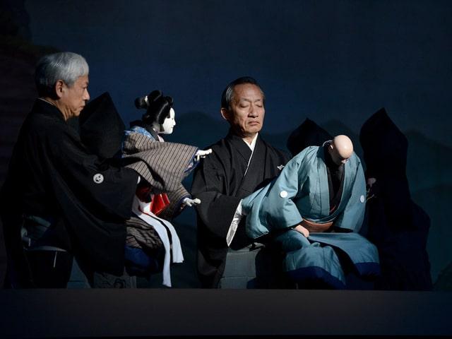 Zwei Männer bewegen zwei japanische Theaterpuppen