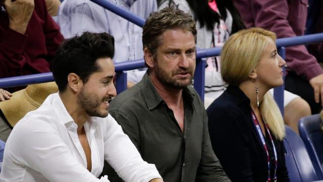 Gerard Butler sitzt auf den Zuschauerrängen und schaut angespannt aufs Feld, links ein Mann, rechts eine Frau.