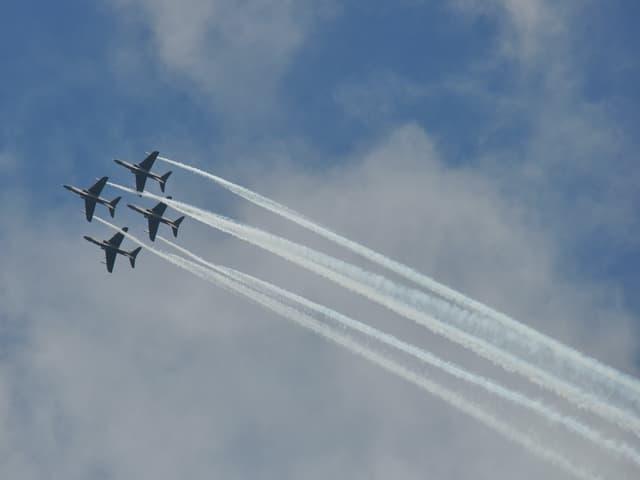 Vier Flugzeuge nebeneinander am Himmel.