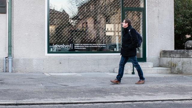 Ein Mann geht auf einem Trottoir an einem Schaufenster vorbei.