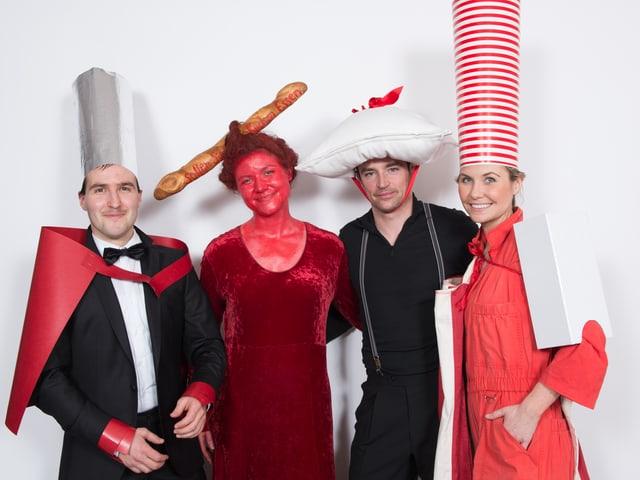 Zwei Frauen und zwei Männer in rot-schwarzen Kostümen.