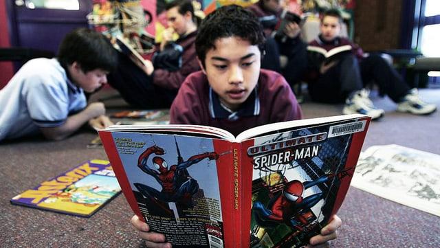 Ein Schüler in Neuseeland liest einen Spider-Man Comic.