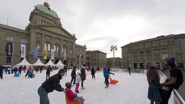 Eisbahn mit Leuten auf dem Eis. Dahinter das Bundeshaus.