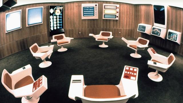 ein Raum mit futuristischen Bildschirmen und Sesseln