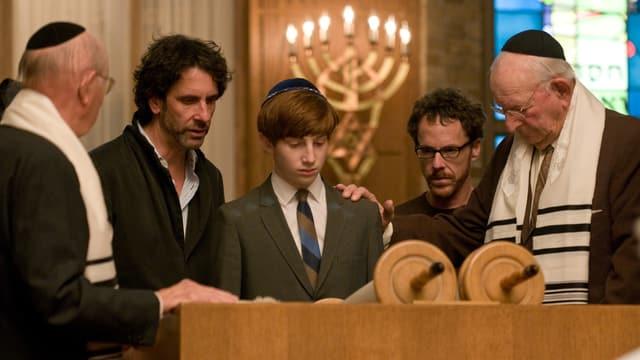 Das Produktionsfoto zeigt eine Szene, in der ein Dreizehnjähriger in der Synagoge bei der traditionellen Bar-Mizwa: der Junge steht in der Mitte vor dem Pult, auf dem die Tora liegt, rechts und links von ihm die Regisseure, umrahmt von zwei alten Herren, den Vorbetern. Alle blicken leicht zu Boden und scheinen konzentriert.