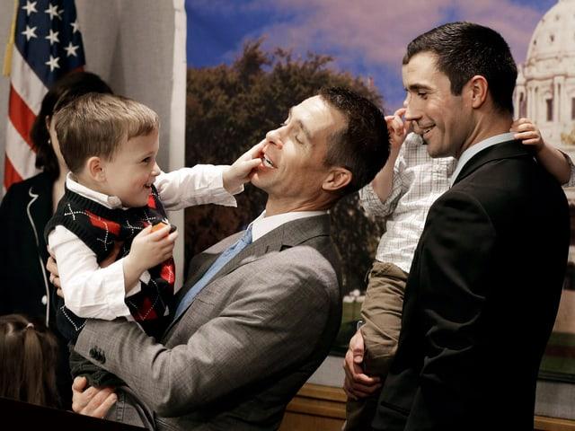 Zwei Männer tragen lachend ihre Söhne