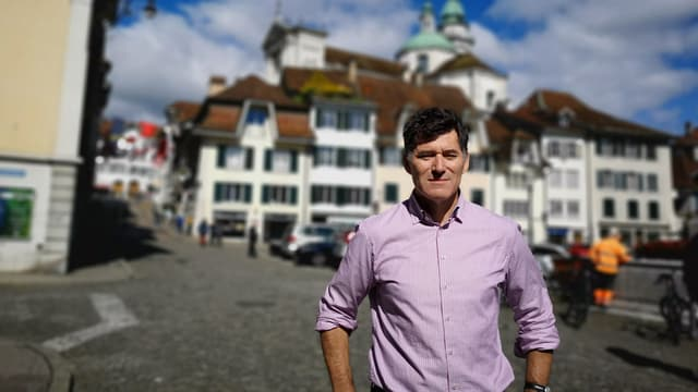 Mann mit weiss-rotem Hemd vor der Altstadt von Solothurn.