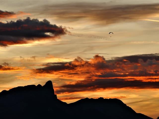 Leicht bewökter Himmel in rot und lila. Ganz klein ist ein Gleitschirm in der Luft zu sehen.