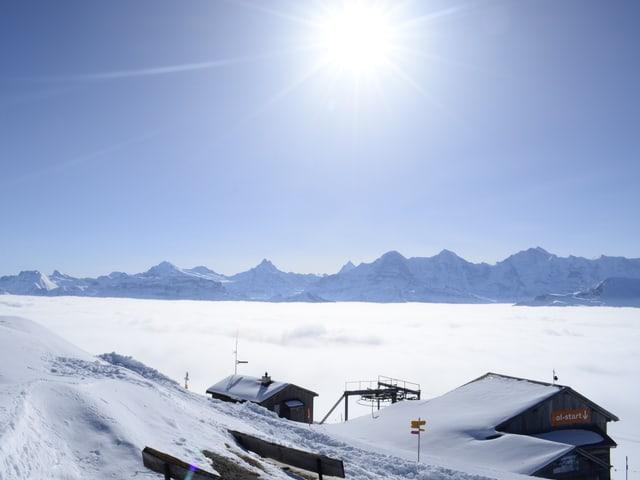 Bergstation einer Seilbahn, dahinter Nebelmeer, wieder dahinter Alpengipfel. Darüber blauer Himmel.