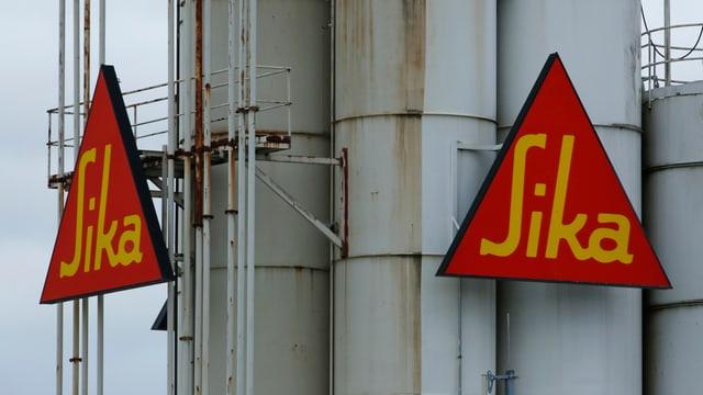 Zwei dreieckige Sika-Logo an einem grauen Stahlturm