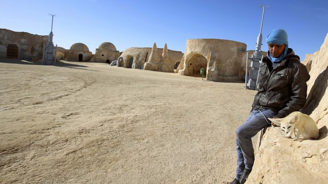 Junger Mann mit Wüsten Hund vor Steinbauten