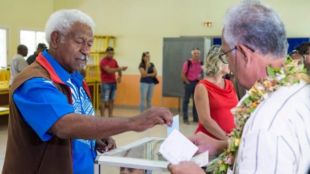 Zwei Männer legen ihre Stimmzettel in die Wahlurnen.