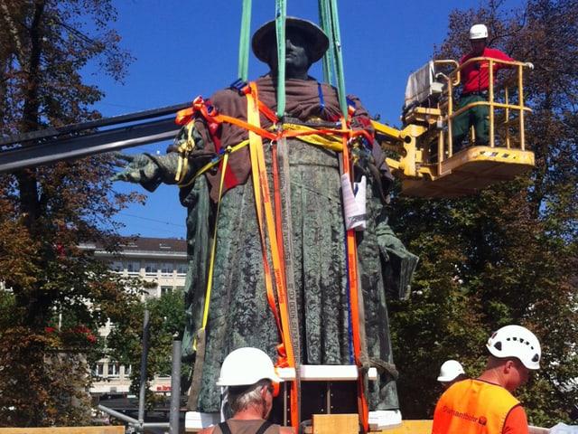 Ein Mann auf einem Krahn befestigt die Vadian-Statue mit Seilen am Krahn.